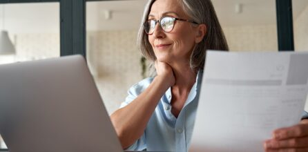 Smiling middle aged woman using laptop computer