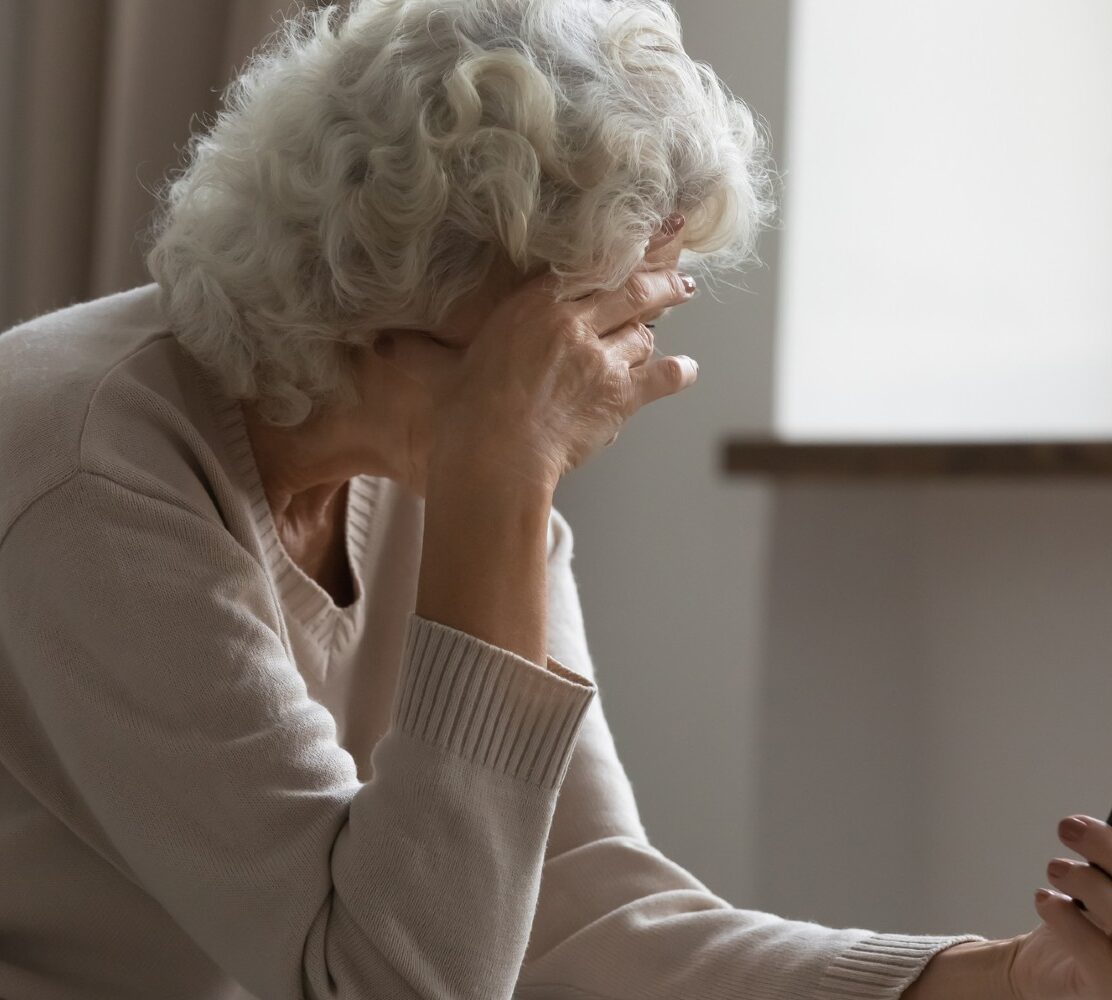 Elderly woman on the phone, holding her head in her hand